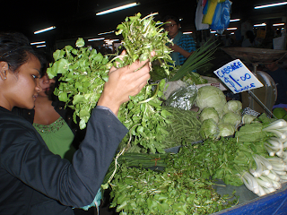 woman looking at watercress in market
