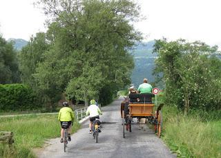 Cyclists passing a horse-drawn carriage, Liechtenstein.