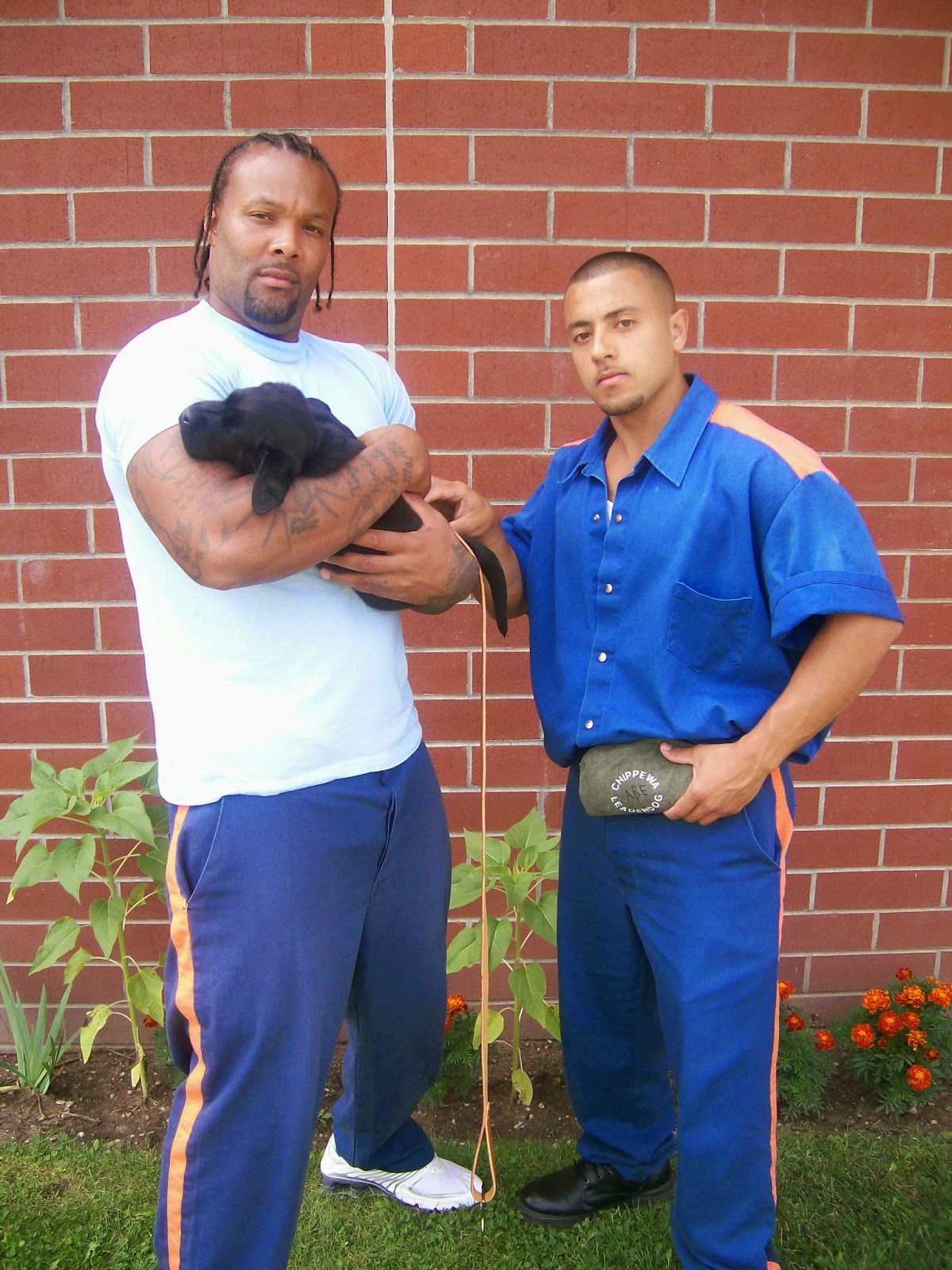 Two  men stand in front of a brick wall, the african american man on the left is wearing blue prison pants and a white t-shirt, he is holding a small black lab puppy in his arms. The man on the right is wearing the blue prison uniforms. They have serious looks on their faces.