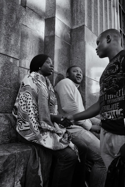 A man shakes hands with a woman while another man looks on in this South African Street photo