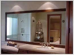 en esta otra miaguen vemos otro espejo mas grande sobrepuesto en el muro del bao con un marco de madera oscura color cafe este espejo refleja una mayor