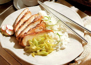 Chicken breasts in a teriyaki marinade served sliced with sticky rice and leeks