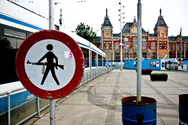 A train and a machine gun road sign outside of Amsterdam Centraal Station on a very cold morning.