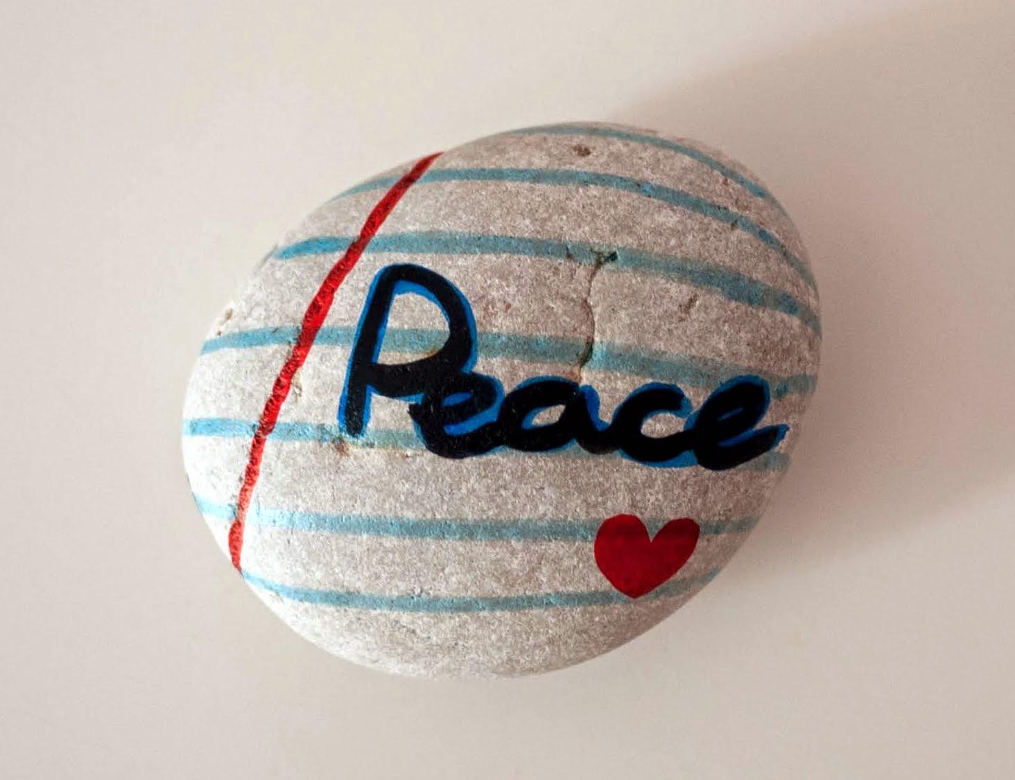 """Piedra con con la palabra """"Peace"""" pintada encima y un corazoncito dibujado en una pauta de hoja escolar."""