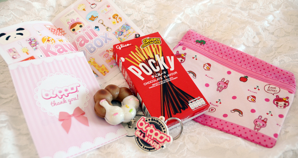 The items that I got from Blippo: a squishy donut charm, zippered pink pouch, chocolate Pocky, and complimentary keychain.