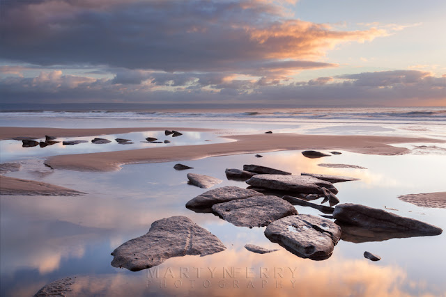 Clouds reflect around beach rocks at Dunraven Bay in South Wales at Sunset by Martyn Ferry Photography