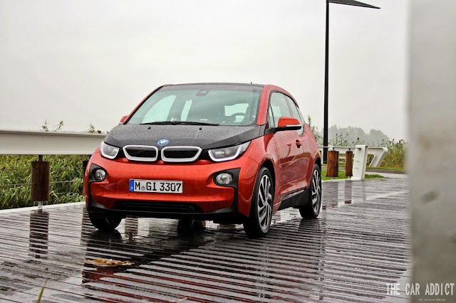 orange BMW i3 on a Bridge between Amsterdam and Alsmeer during Rain by Lisa the Car Addict