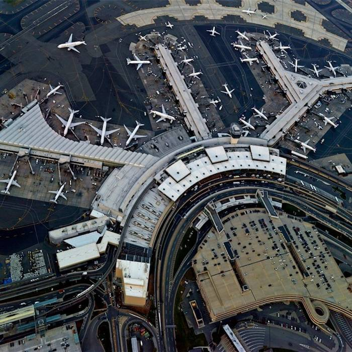 "Jeffrey Milstein Aerial Shots of  International Airport, The series displays ""the patterns, layering and complexity of cities, and the circulation patterns for travel, such as waterways, roads, and airports that grow organically over time much like a living organism."" The interweaving roads and geometric presentation viewed in the collection is a unique sight to be seen from a bird's-eye view. While exhilarating to be moving in midair, the images exhibit the beautiful downtime and landing marks for airplanes."