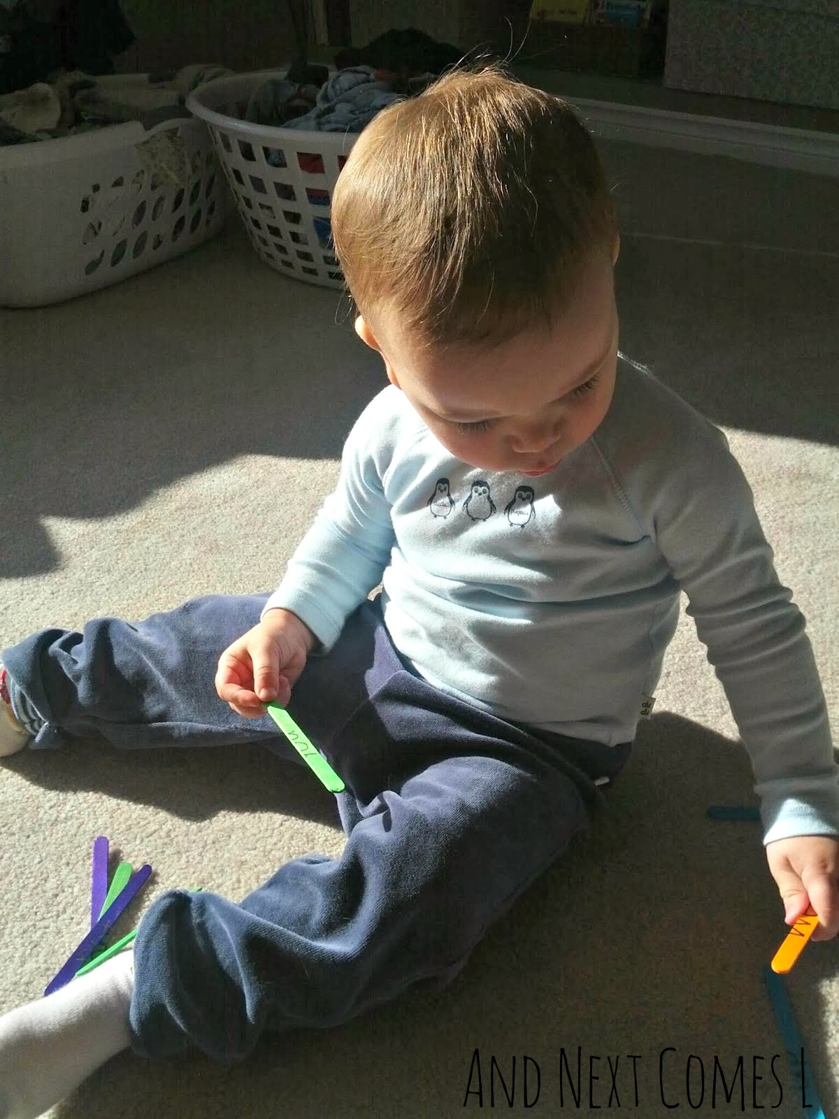 Toddler playing with craft sticks from And Next Comes L