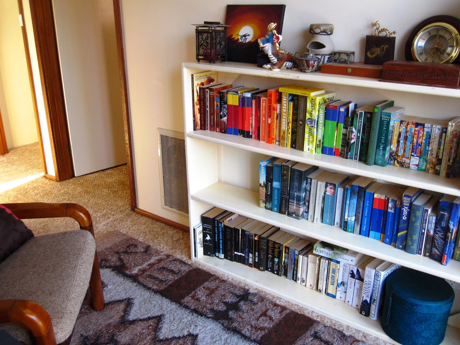 A reading nook which includes a 1970s comfy chair and floor rug, and a long cream bookcase containing books in colour order and with an arrangement of brown-themed items on top.