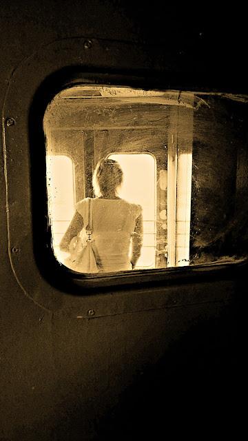 Девушка в тамбуре электрички, собирается выходить на станции Ржевская. Около-железнодорожное. Фотография черно-белая сепия грязное стекло темный светлый двери вагон