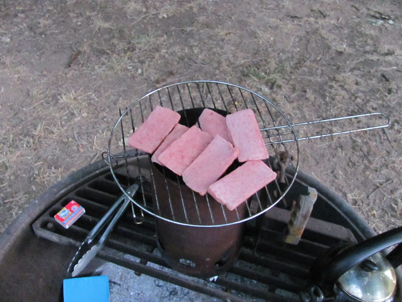 Slices of SPAM cook on a grate over the charcoal chimney at Casswell State Park, California
