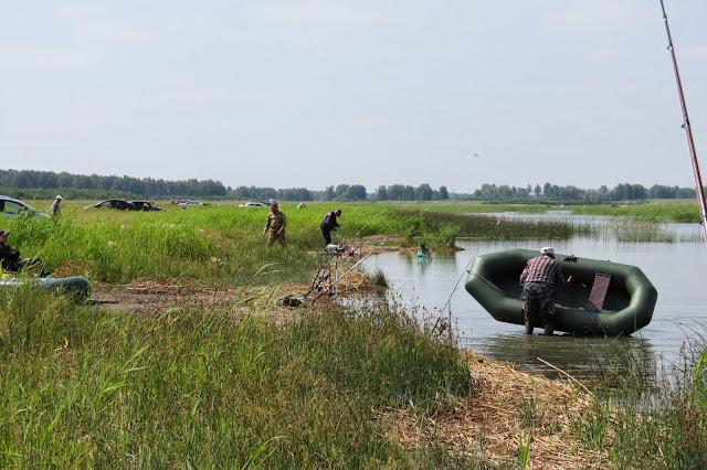 Мужик достаёт лодку из озера Яу-Балык