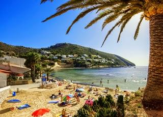 Zomerse topdrukte strand El Portet in  Moraira aan de Costa Blanca in Spanje.