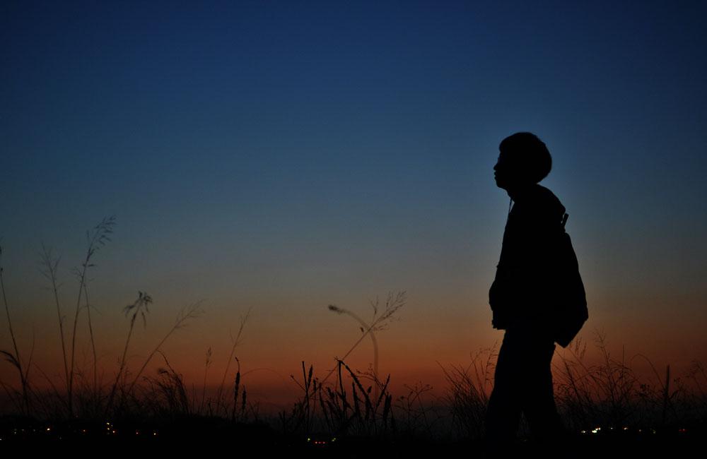 日が沈む時、河原を歩くの写真
