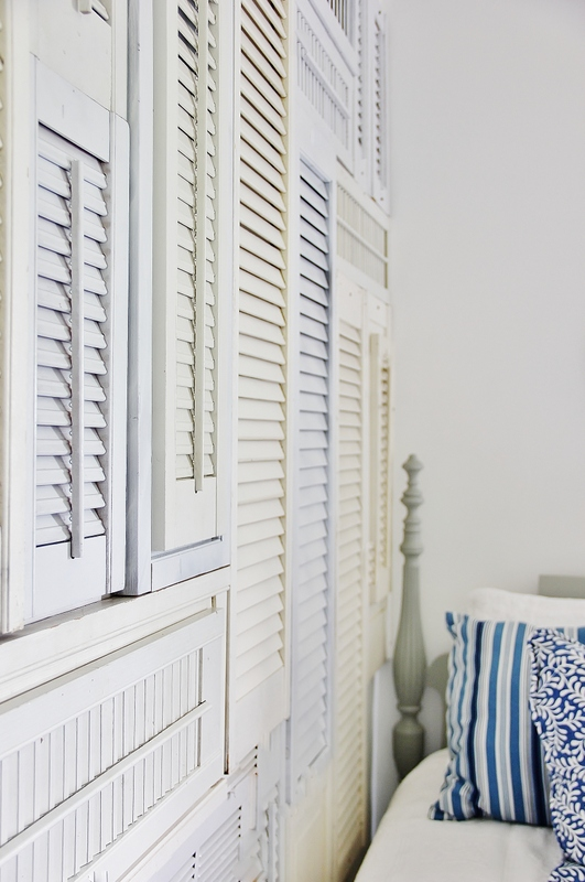 Old shutters wall art in a bedroom by Thistlewood Farms featured on I Love That Junk