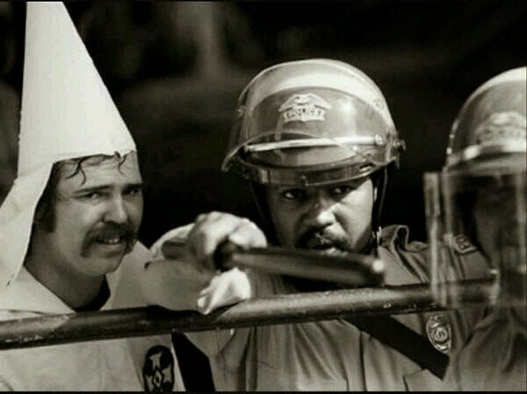 24 Rare Historical Photos That Will Leave You Speechless - A black police officer protects a member of the KKK during a rally in 1983.