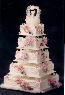 5 tier white square wedding cake with pink flowers