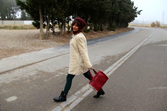 caminando con look en verde y burdeos con abrigo pelo y botas moteras