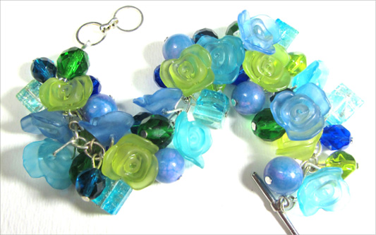 Chunky bracelet has blue and green flower buttons with fire polished czech beads and crackle beads