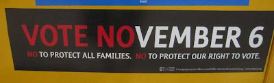 Bumpersticker reading VOTE NO VEMBER on both amendments