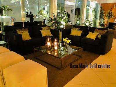 mesa de centro espelhada, veas, mini arranjo amarelo, sofá preto, puff bege