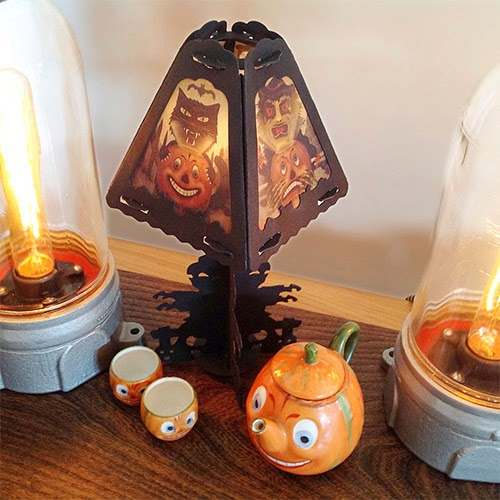 German Teapot and Cups under vintage-style Halloween lantern by Bndlegrim with panes featuring Jack O'Lanterns, Black Cat, and Witch
