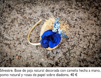 Tocado con base de paja natural decorada con camelia artesanal, pomo natural y rosas de papel sobre diadema