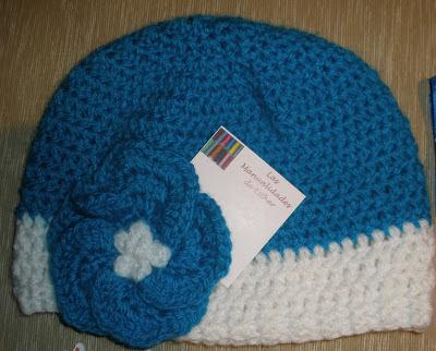 Gorro con lanas turquesa y blanca realizado a crochet y adornado con un floripondio también a crochet