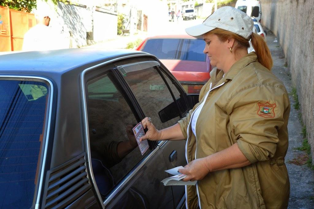 Guardas municipais Michel Santana e Jania Gonçalves atuam adesivando os carros
