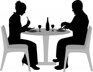 Black and white silhouette of couple eating and drinking at a dining table