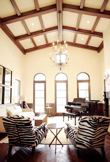 Living room with super high ceilings, exposed beams, arched windows, herringbone wood parquet floors, a piano, and very neutral furnishings except for two upholstered zebra print chairs
