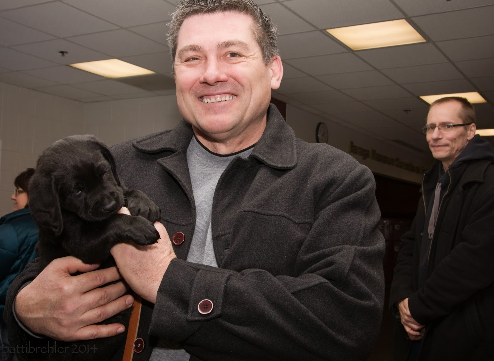 The samll black lab is now being held in the arms of another man. The shot is taken from his chest up. The man is wearing a black jacekt and grey sweatshirt. He has short dark hair and is smiling at the camera. The puppy looks relaxed and has his front paws on the man's lett hand. In the background is the man with glasses from the first photo. He is standing on the right side looking at the man with the puppy and is smiling. He is holding his hands together in front of him. At the top on either side of the man holding the puppy are the lights in the white tiled ceiling.
