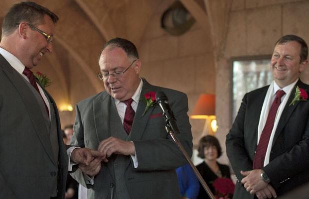 Ministro australiano Ian Hunter (centro), de Inclusão Social, coloca o anel na mão de seu marido, Leith Semmens, no casamento realizado nesta quarta (19) (Foto: Jorge Guerrero/AFP)