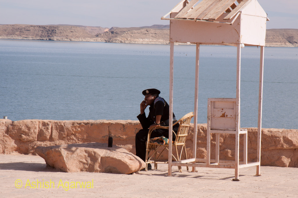 Policeman using the phone at a security post next to the Abu Simbel temple in South Egypt