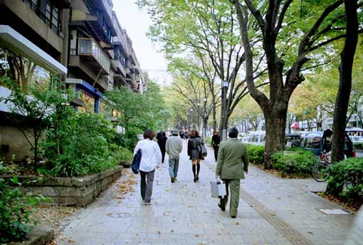 People walking down urban street lined with apartments.