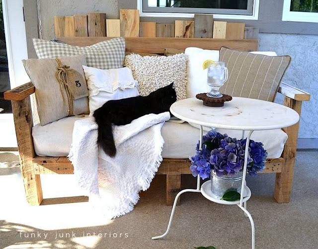 Pallet wood sofa and bistro table with hydrangeas on FunkyJunkInteriors.ne