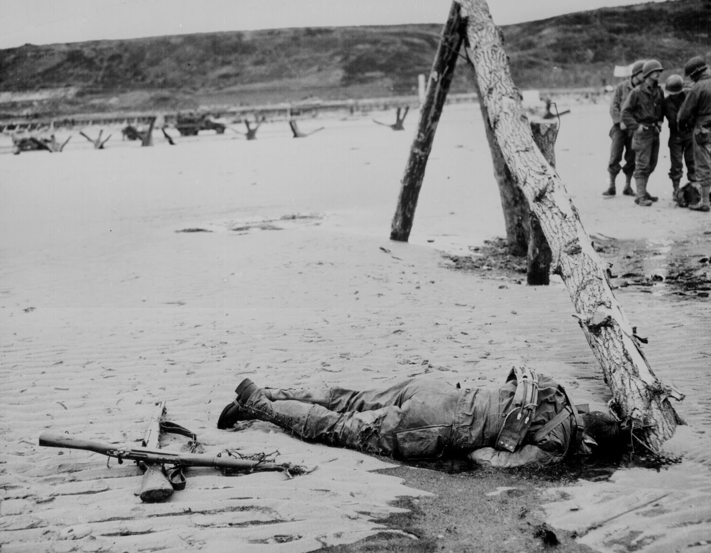 Crossed rifles in the sand are a fallen comrade's tribute, 1944