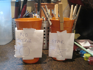 Clothes-pegs on cups reward system for star chart