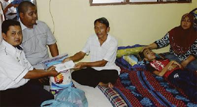 PRIHATIN...kakitangan Baitulmal Pejabat Agama Mersing menyerahkan sumbangan kepada bapa Amirul.