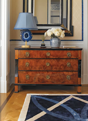 luxury foyer design look striking with its wood patterned desk and serene details