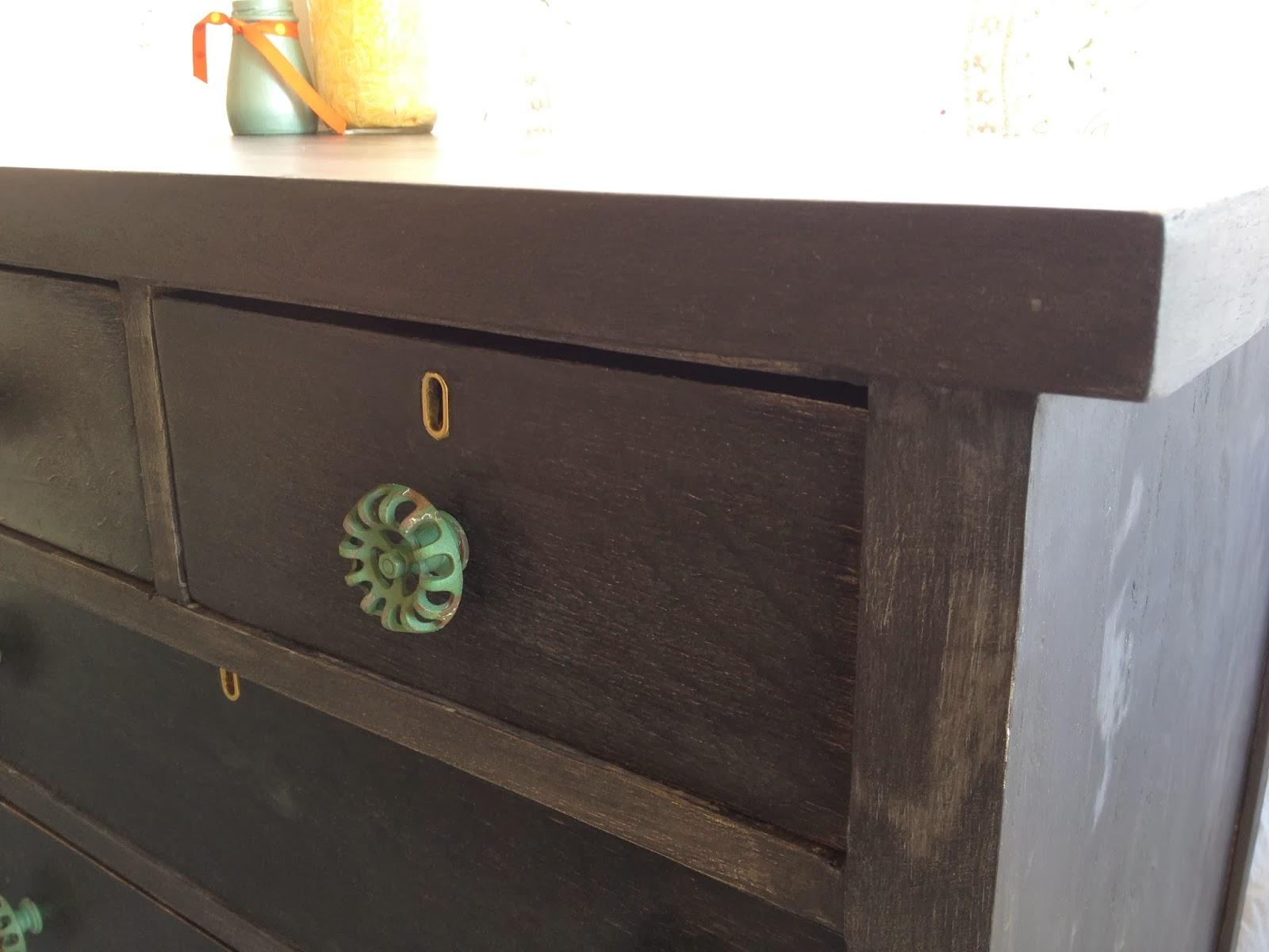 black antique dresser with green knobs hose