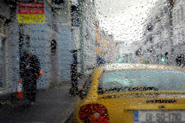 Galway city in the rain, people walking, taxi waiting