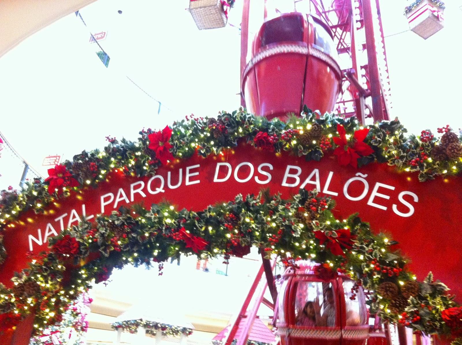 Descrição da Foto: Um arco vermelho escrito em branco NATAL PARQUE DOS BALÕES, COM folhas e flores vermelhas em volta. No fundo cabines da roda-gigante.
