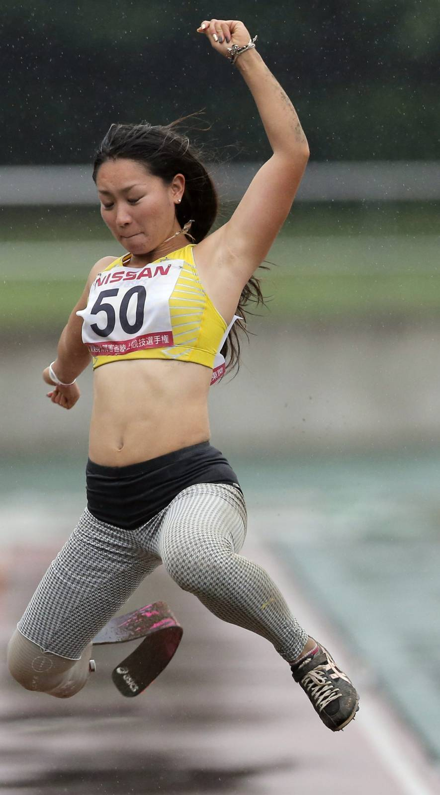 In this photo taken Saturday, July 7, 2012, Paralympic athlete Maya Nakanishi wearing her new racing blade competes in the women's long jump final event at the 17th Handicapped Truck and Field Championships in Tokyo.