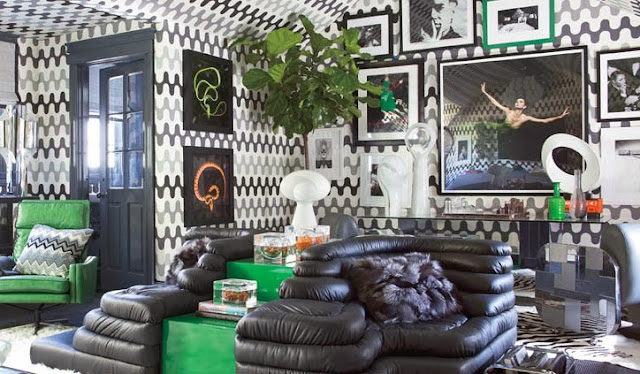 Retro guest apartment with black and green furniture, grey and white graphic print wall covering and lots of art