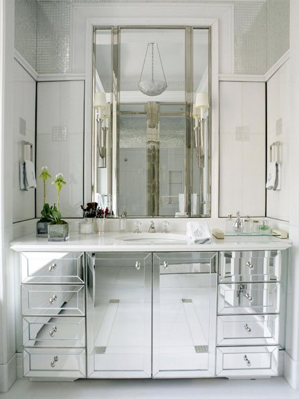 bathroom with mirrored sink cabinets and a crystal pendant light