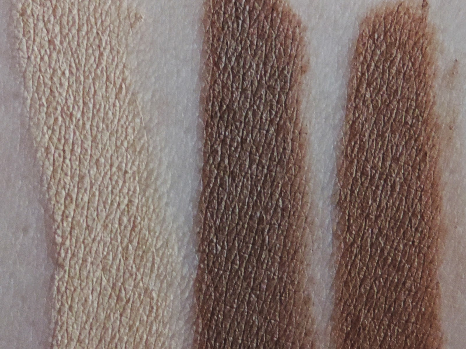 Swatches of Smashbox Step By Step Contour Stick Trio (from left) Highlighter, Contour, Bronze