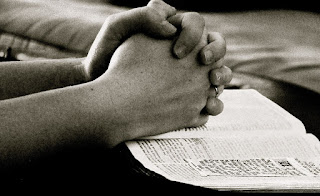 hands clasped in prayer resting on a Bible