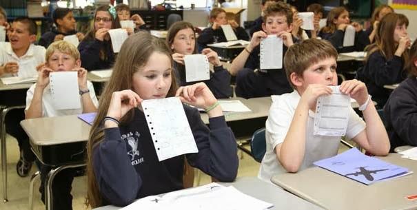 Los niños en clase probando el experimento de levantar un papel atraido por el aire